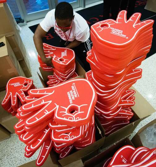 Workers prepare stacks of foam hands displaying a 3-point gesture to hand out to fans entering the a