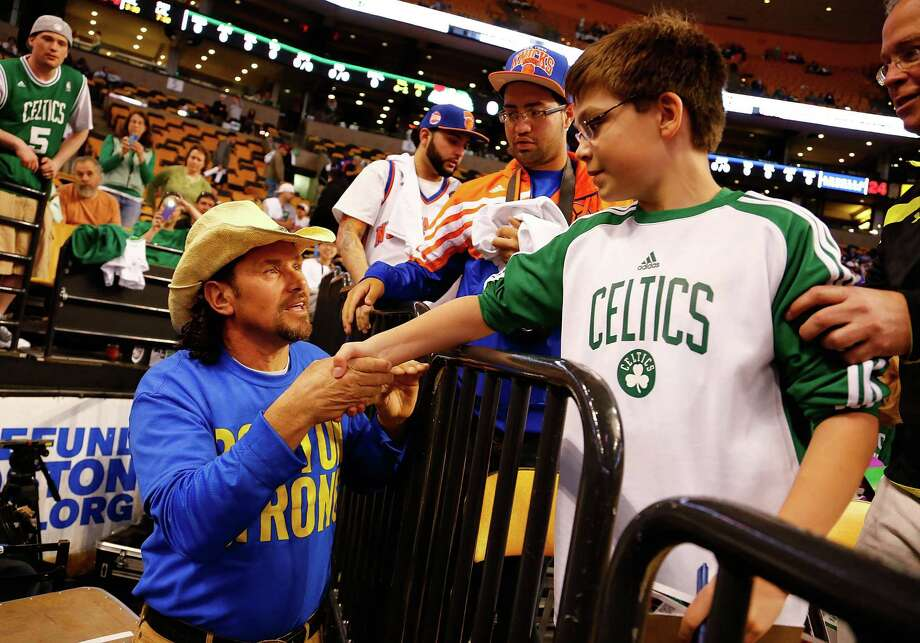 BOSTON, MA - APRIL 28: Carlos Arredondo, the cowboy hat hero from the Boston Marathon bombings, shakes hands with a young fan prior to Game Four of the Eastern Conference Quarterfinals of the 2013 NBA Playoffs between the Boston Celtics and the New York Knicks on April 28, 2013 at TD Garden in Boston, Massachusetts. NOTE TO USER: User expressly acknowledges and agrees that, by downloading and or using this photograph, User is consenting to the terms and conditions of the Getty Images License Agreement. Photo: Jared Wickerham, Getty Images / 2013 Getty Images