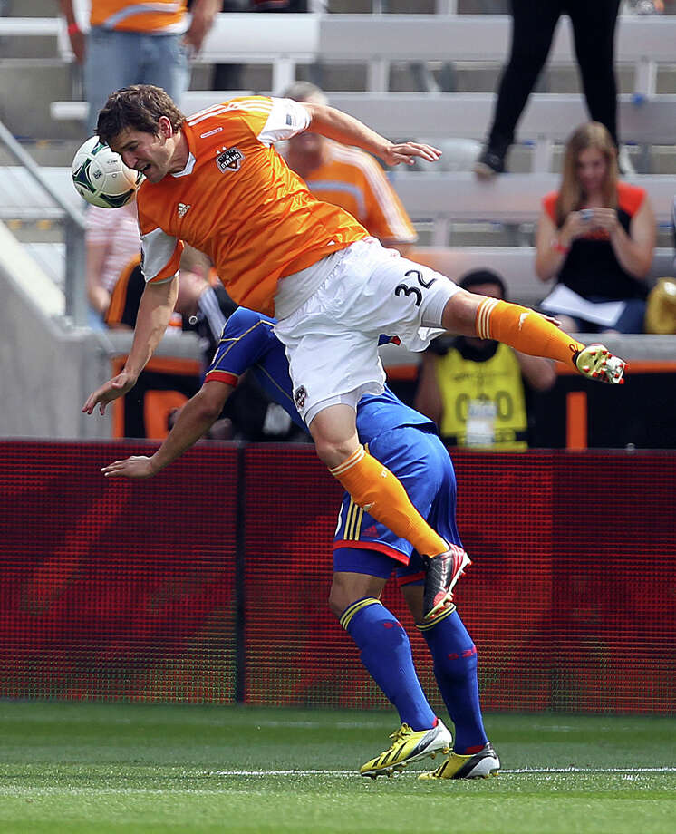 Houston Dynamo defender Bobby Boswell, front, falls over Colorado Rapids midfielder as he tries to control the ball on a header during the first half of a MLS soccer game, Sunday, April 28, 2013, in BBVA Compass Stadium in Houston. Photo: Nick De La Torre, Chronicle / © 2013 Houston Chronicle