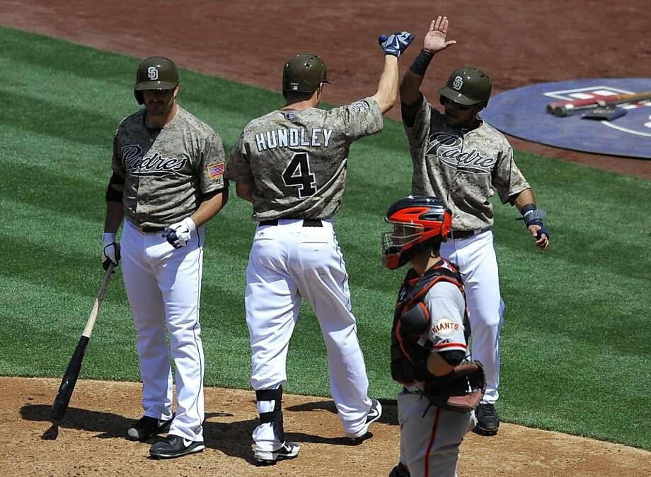 SAN DIEGO, CA - APRIL 28:  Nick Hundley #4 of the San Diego Padres is congratulated by Alexi Amarista #5 (R) as Jason Marquis #21 (L) and Buster Posey #28 of the San Francisco Giants look on after Hundley hit a two-run homer  during the second inning of a baseball game at Petco Park on April 28, 2013 in San Diego, California.  (Photo by Denis Poroy/Getty Images) Photo: Denis Poroy, Getty Images