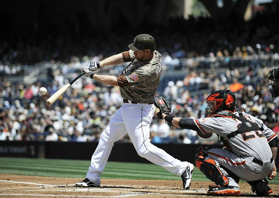 SAN DIEGO, CA - APRIL 28:  Chase Headley #7 of the San Diego Padres hits a solo home run as Buster Posey #28 of the San Francisco Giants looks on during the first inning of a baseball game at Petco Park on April 28, 2013 in San Diego, California.  (Photo by Denis Poroy/Getty Images) Photo: Denis Poroy, Getty Images