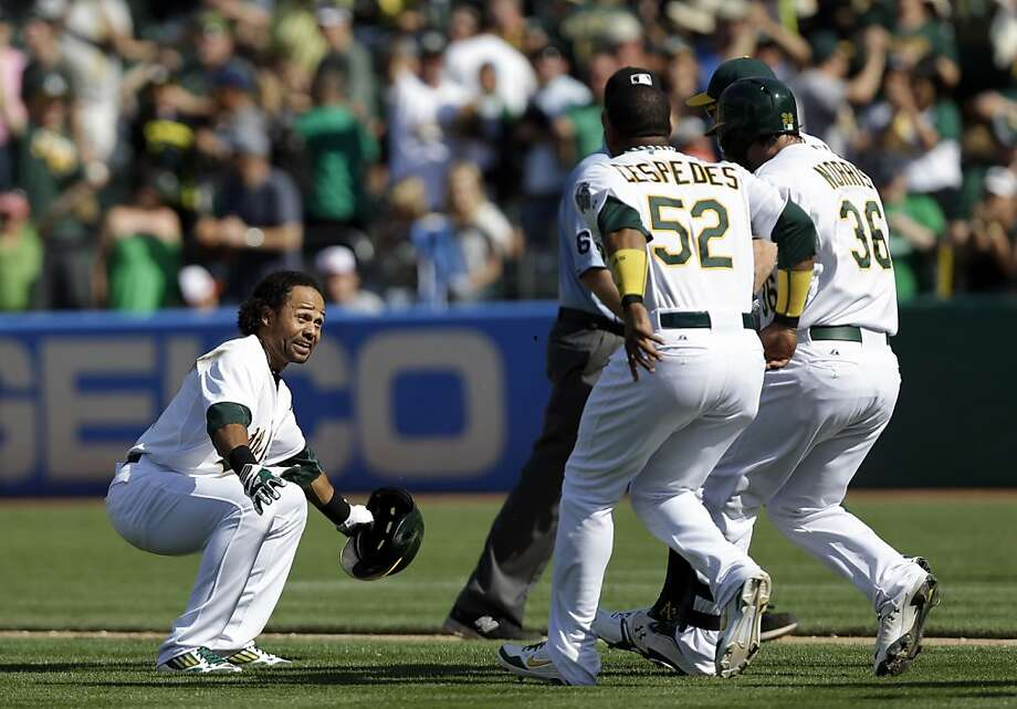Oakland Athletics' Coco Crisp, left, celebrates with Yoenis Cespedes (52) and Derek Norris (36) after Crisp's sacrifice bunt drove in the winning run against the Baltimore Orioles during the 10th inning of a baseball game, Sunday, April 28, 2013, in Oakland, Calif. The Athletics' Eric Sogard scored on Crisp's bunt after a throwing error to third base from Orioles' Manny Machado. Oakland won 9-8. (AP Photo/Marcio Jose Sanchez) Photo: Marcio Jose Sanchez, Associated Press