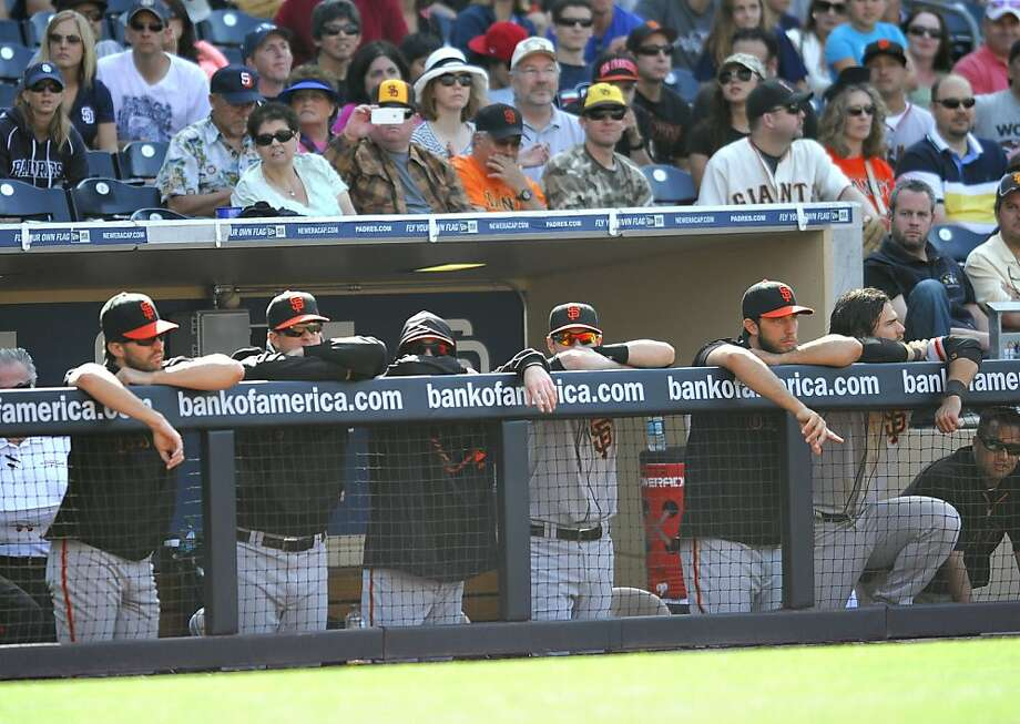 A subdued line of Giants watches the final half-inning of the Padres' three-game sweep in San Diego. Photo: Denis Poroy, Getty Images
