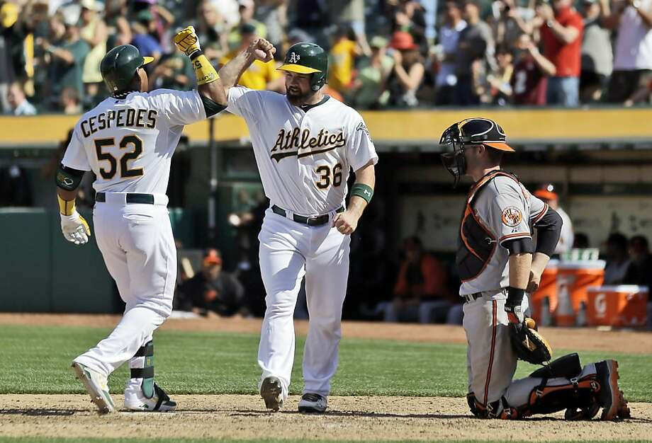 Oakland Athletics' Yoenis Cespedes, left, celebrates with Derek Norris (36) after tying a baseball game 8-8 with a two-run home run against the Baltimore Orioles during the ninth inning on Sunday, April 28, 2013, in Oakland. Calif. Oakland won 9-8 in 10 innings. (AP Photo/Marcio Jose Sanchez) Photo: Marcio Jose Sanchez, Associated Press