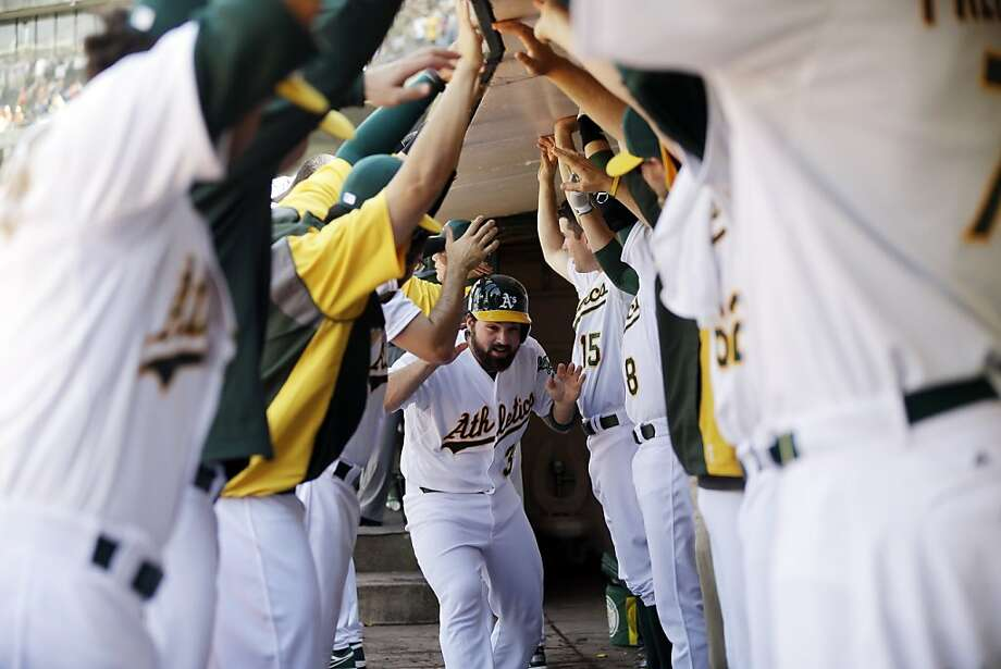 Oakland Athletics' Derek Norris, center, celebrates with teammates in the dugout after being driven in with a two-run home run from Yoenis Cespedes during the ninth inning of a baseball game against the Baltimore Orioles, Sunday, April 28, 2013, in Oakland, Calif. Oakland won 9-8 in 10 innings. (AP Photo/Marcio Jose Sanchez) Photo: Marcio Jose Sanchez, Associated Press