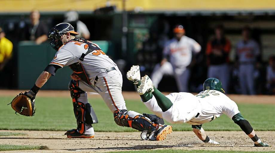Oakland Athletics' Eric Sogard, right, scores the winning run past Baltimore Orioles catcher Matt Wieters, left, on a sacrifice-bunt from Coco Crisp and throwing error from the Orioles' Manny Machado during the 10th inning of a baseball game, Sunday, April 28, 2013. Oakland won 9-8. (AP Photo/Marcio Jose Sanchez) Photo: Marcio Jose Sanchez, Associated Press