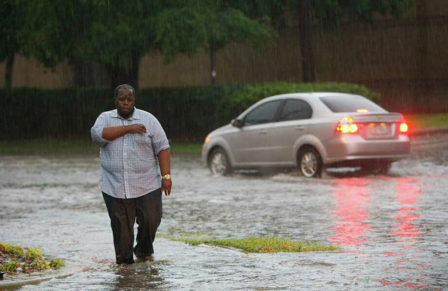 Jase Ray walks along Fannin Street, which became flooded after an afternoon downpour, in southwest Houston on Saturday. Photo: UWN