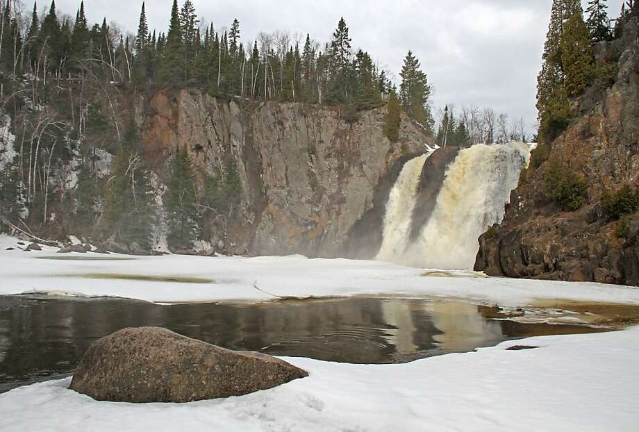High Falls on the Baptism River in Tettegouche State Park, near Silver Bay, Minn., is open and raging on Sunday, April 28, 2013. Ice on the river above and below the falls was slowly starting to erode from the sun and above-normal temperatures. Waterfalls along Minnesota's North Shore have opened up the past few days. (AP Photo/The Duluth News-Tribune, Andrew Krueger) Photo: Andrew Krueger, Associated Press