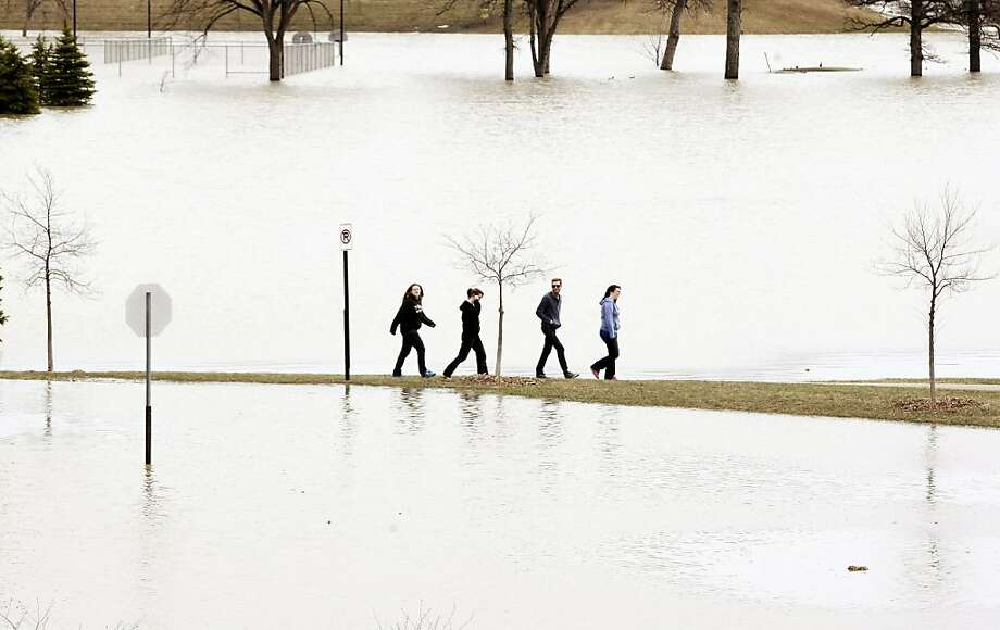 People walk on a narrow strip of land between the flooded Woodlawn Park, background, and the rising Red River, foreground, Sunday, April 28, 2013, in Moorhead. (AP Photo/The Forum, Dave Wallis) Photo: Dave Wallis, Associated Press