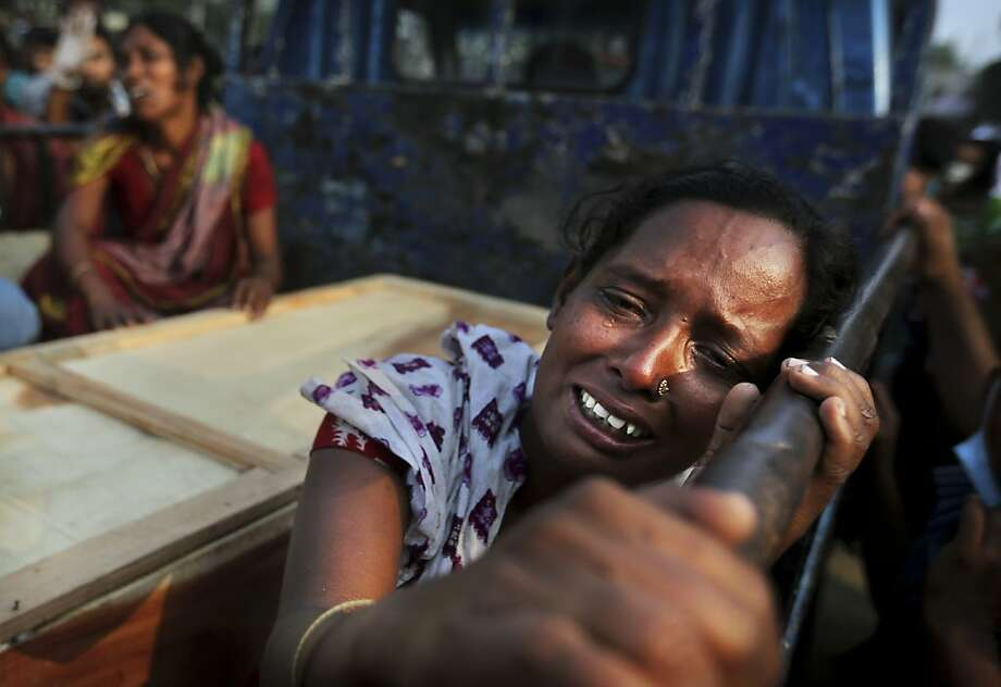 A Bangladeshi woman weeps as she sits next to the coffin of a relative who died in a building that collapsed Wednesday in Savar, near Dhaka, Bangladesh, Sunday, April 28, 2013. A fire broke out late Sunday in the wreckage of the garment factory that collapsed last week in Bangladesh killing hundreds, with smoke pouring from the piles of shattered concrete and some of the rescue efforts forced to stop.(AP Photo/Kevin Frayer) Photo: Kevin Frayer, Associated Press