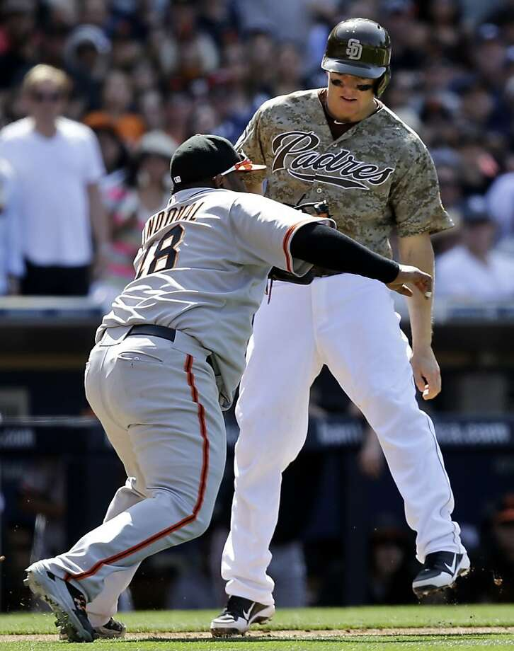 San Diego Padres' Nick Hundley is tagged out by San Francisco Giants third baseman Pablo Sandoval after being caught in a rundown while trying to score from third in the sixth inning of a baseball game in San Diego, Sunday, April 28, 2013. (AP photo/Lenny Ignelzi) Photo: Lenny Ignelzi, Associated Press