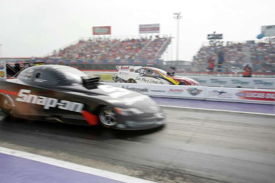 Cruz Pedregon, left, edges Tim Wilkerson in the final round of the Funny Car competition on Sunday. Photo: Eric Kayne / 2013 Eric Kayne