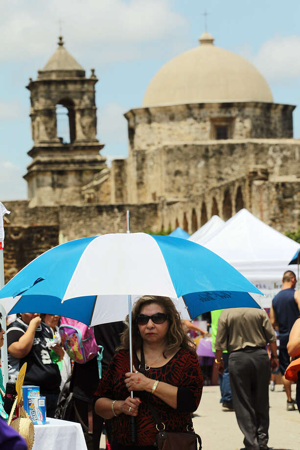 As the day turns sunny, Janie Tarin uses an umbrella amid the sprawling crowd behind Mission San José Church during MissionFest. Hundreds of patrons attended the event that began as a church festival at Mission County Park. Photo: Jerry Lara / San Antonio Express-News