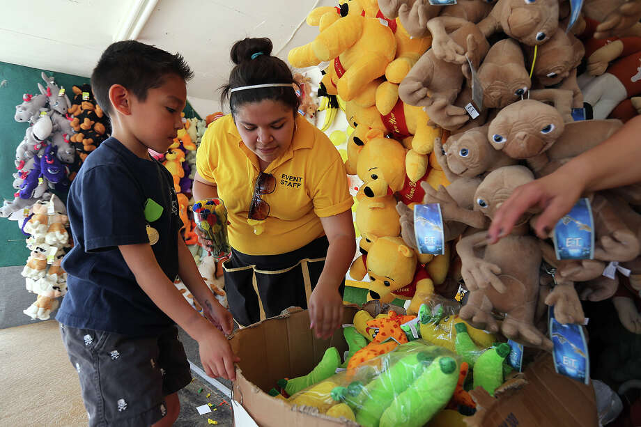 Jake Sepulveda, 7, gets help selecting a prize after winning at a dart game during San Jose MissionFest, Sunday, April 28, 2013. Helping Sepulveda is RaeAnna Cardenas. Photo: San Antonio Express-News / © 2013 San Antonio Express-News