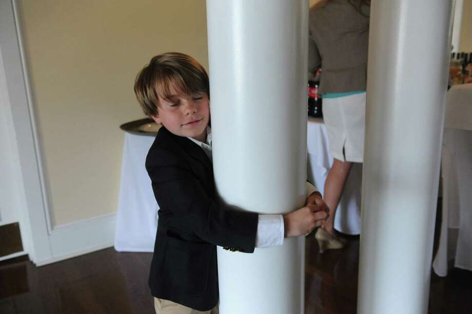 Niels Kjaernested, 5, hugs a pillar at the Belle Haven Club at Greenwich, Sunday, April 28, 2013. The Greenwich Historical Society celebrate the 25th anniversary of its Greenwich Landmark program of recognizing houses with a reception at the Belle Haven Club, by presenting a plaque to the Club as a Greenwich landmark site for over a century. Five other structures to receive plaques to mark their value to Greenwich's heritage. Photo: Helen Neafsey / Greenwich Time