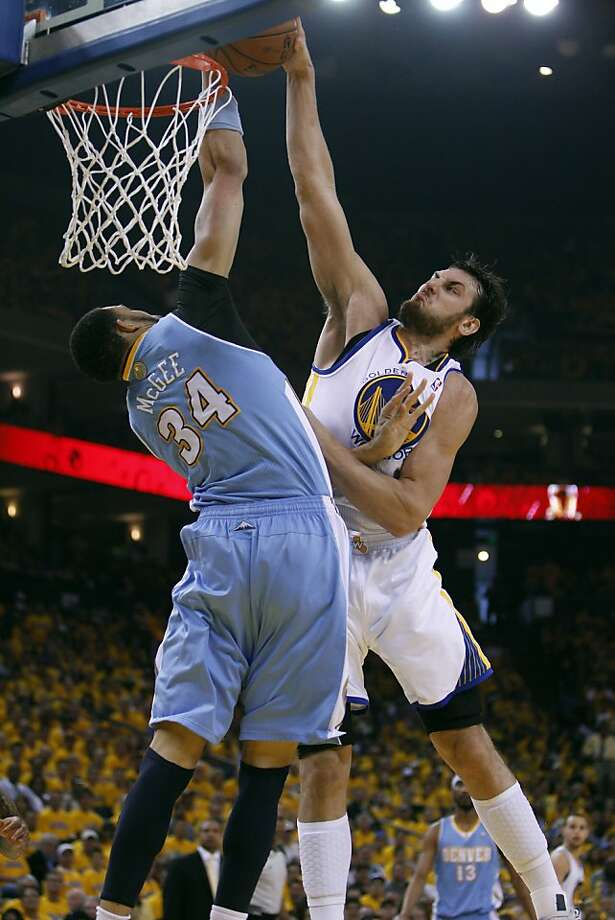 Andrew Bogut (12) dunks over Javale McGee in the first half. The Golden State Warriors played the Denver Nuggets in Game 4 of the first round of the NBA playoffs at Oracle Arena in Oakland, Calif., on Sunday, April 28, 2013. Photo: Carlos Avila Gonzalez, The Chronicle