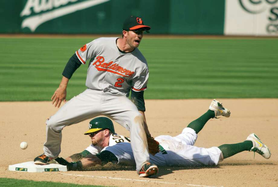 An errant throw allowed Oakland's Eric Sogard to slide into third safely, then score the winning run. Photo: D. ROSS CAMERON, MBR / Contra Costa Times