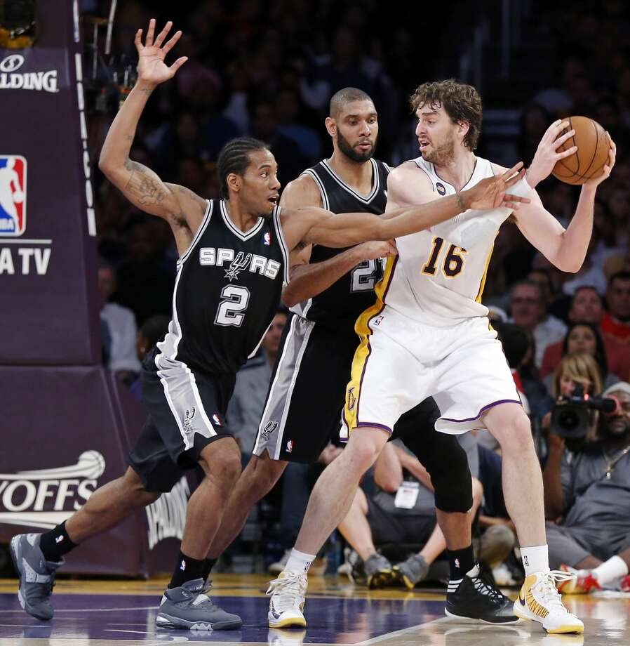 San Antonio Spurs' Kawhi Leonard and San Antonio Spurs' Tim Duncan defend Los Angeles Lakers' Pau Gasol during first half action of game 4 in the first round of the NBA Playoffs Sunday April 28, 2013 at the Staples Center in Los Angeles, CA.