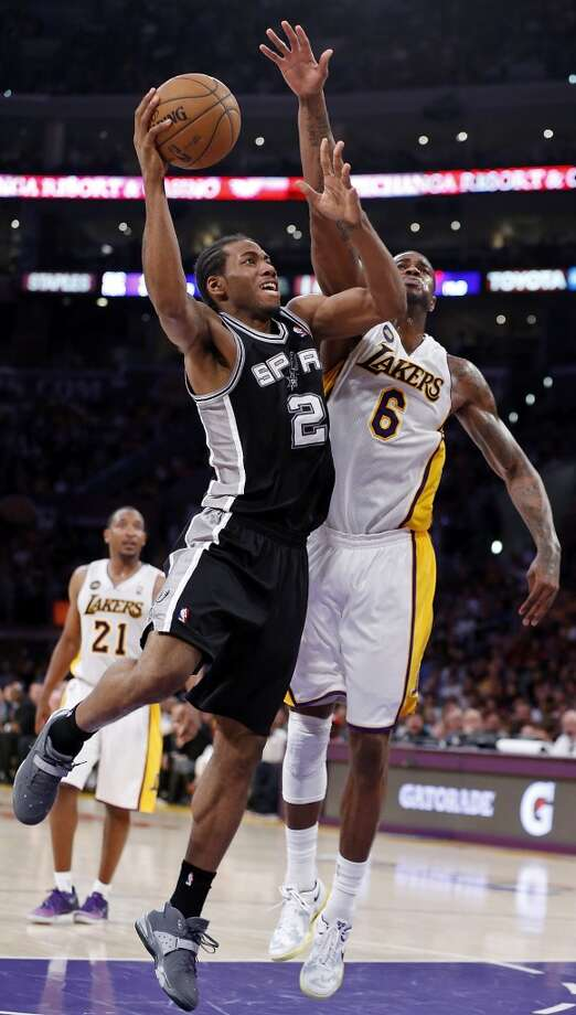 San Antonio Spurs' Kawhi Leonard drives to the basket around Los Angeles Lakers' Earl Clark during second half action of game 4 in the first round of the NBA Playoffs Sunday April 28, 2013 at the Staples Center in Los Angeles, CA. The Spurs won 103-82.