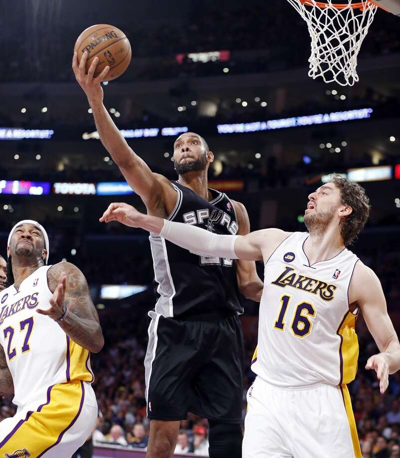 San Antonio Spurs' Tim Duncan grabs a rebound between Los Angeles Lakers' Jordan Hill and Los Angeles Lakers' Pau Gasol during second half action of game 4 in the first round of the NBA Playoffs Sunday April 28, 2013 at the Staples Center in Los Angeles, CA. The Spurs won 103-82.