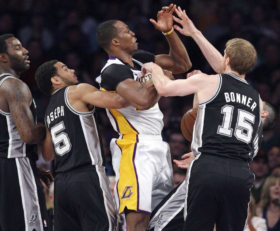 Los Angeles Lakers' Dwight Howard is defended by San Antonio Spurs' DeJuan Blair (from left), San Antonio Spurs' Cory Joseph, San Antonio Spurs' Matt Bonner and San Antonio Spurs' Manu Ginobili during first half action of game 4 in the first round of the NBA Playoffs Sunday April 28, 2013 at the Staples Center in Los Angeles, CA. Joseph was called for a personal foul on the play. Howard was called for a technical foul on the play.