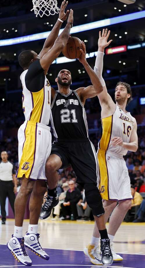 San Antonio Spurs' Tim Duncan drives to the basket between Los Angeles Lakers' Dwight Howard (left) and Los Angeles Lakers' Pau Gasol during second half action of game 4 in the first round of the NBA Playoffs Sunday April 28, 2013 at the Staples Center in Los Angeles, CA. The Spurs won 103-82.