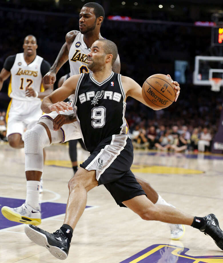 Spurs guard Tony Parker, who finished with 23 points and no turnovers, drives past Lakers forward Earl Clark as Dwight Howard trails during the Spurs' first-round sweep Sunday night at the Staples Center in Los Angeles. Photo: Edward A. Ornelas / San Antonio Express-News