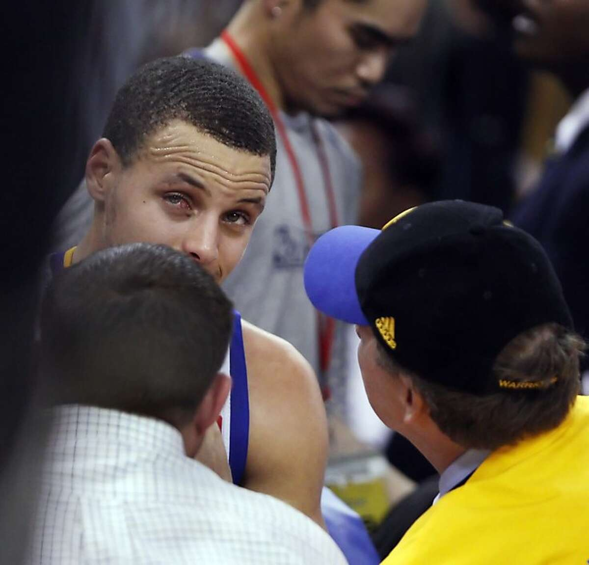 Stephen Curry's eye is examined by team personell in the second half. The Golden State Warriors played the Denver Nuggets in Game 4 of the first round of the NBA playoffs at Oracle Arena in Oakland, Calif., on Sunday, April 28, 2013.