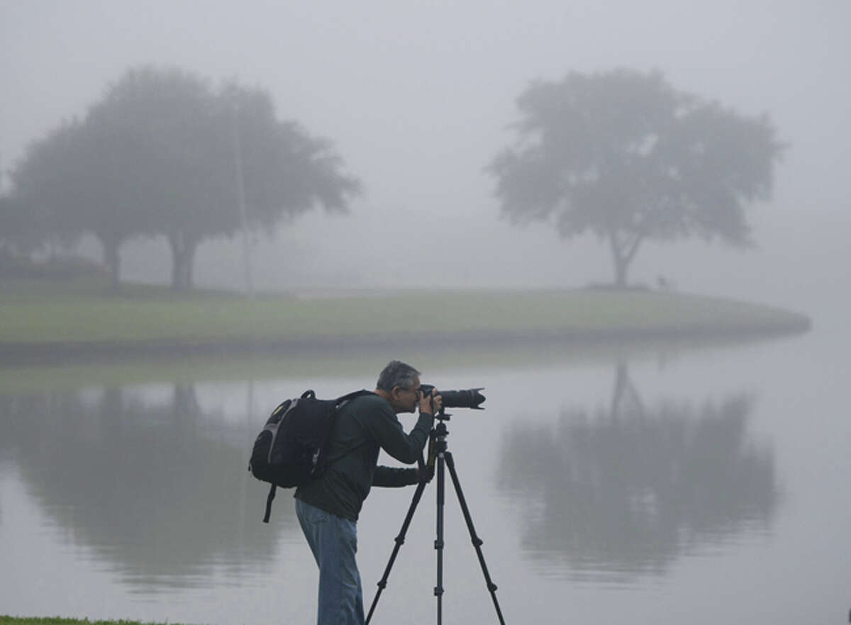 Hung Phan takes advantage of dense morning fog and makes pictures on Southwyck Park lake in Pearland.