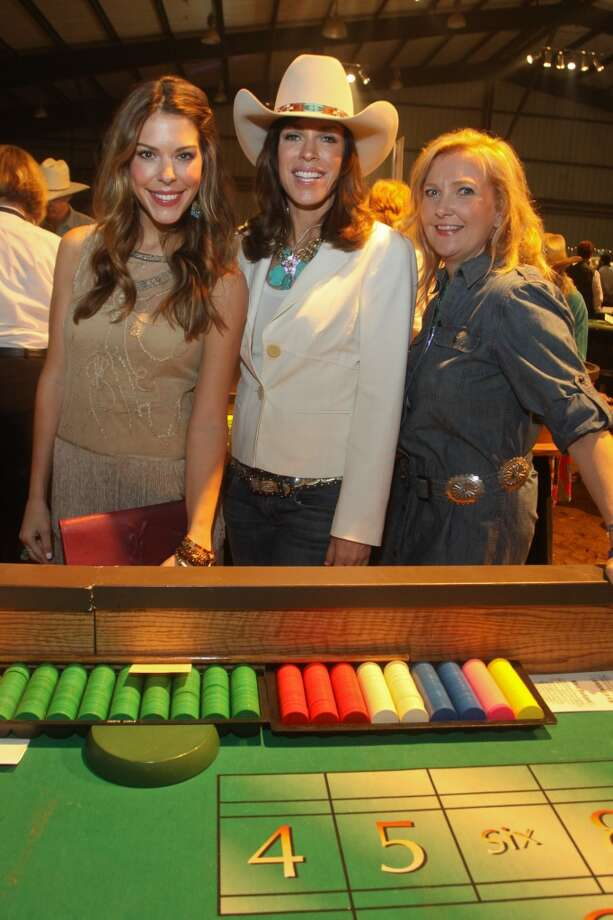 Kendra Smith, from left, Amy Frizzell and Colby Doyle at one of the gaming tables at the Cattle Barons Ball.