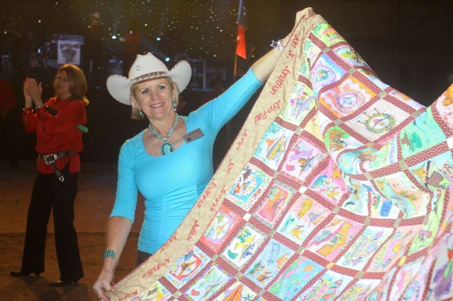 Joan Dunlap holding a quilt for bidding during the auction at the Cattle Barons Ball.