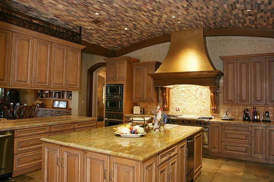 Main kitchen has a barrel ceiling, custom hand painted tiles and Murial and Wood Mode cabinets. Two side by side stainless refrigerators, ice maker, 2 dishwashers, 2 compactors and large island w/sink. Adjoining catering kitchen with walk in cooler Photo: HAR.com
