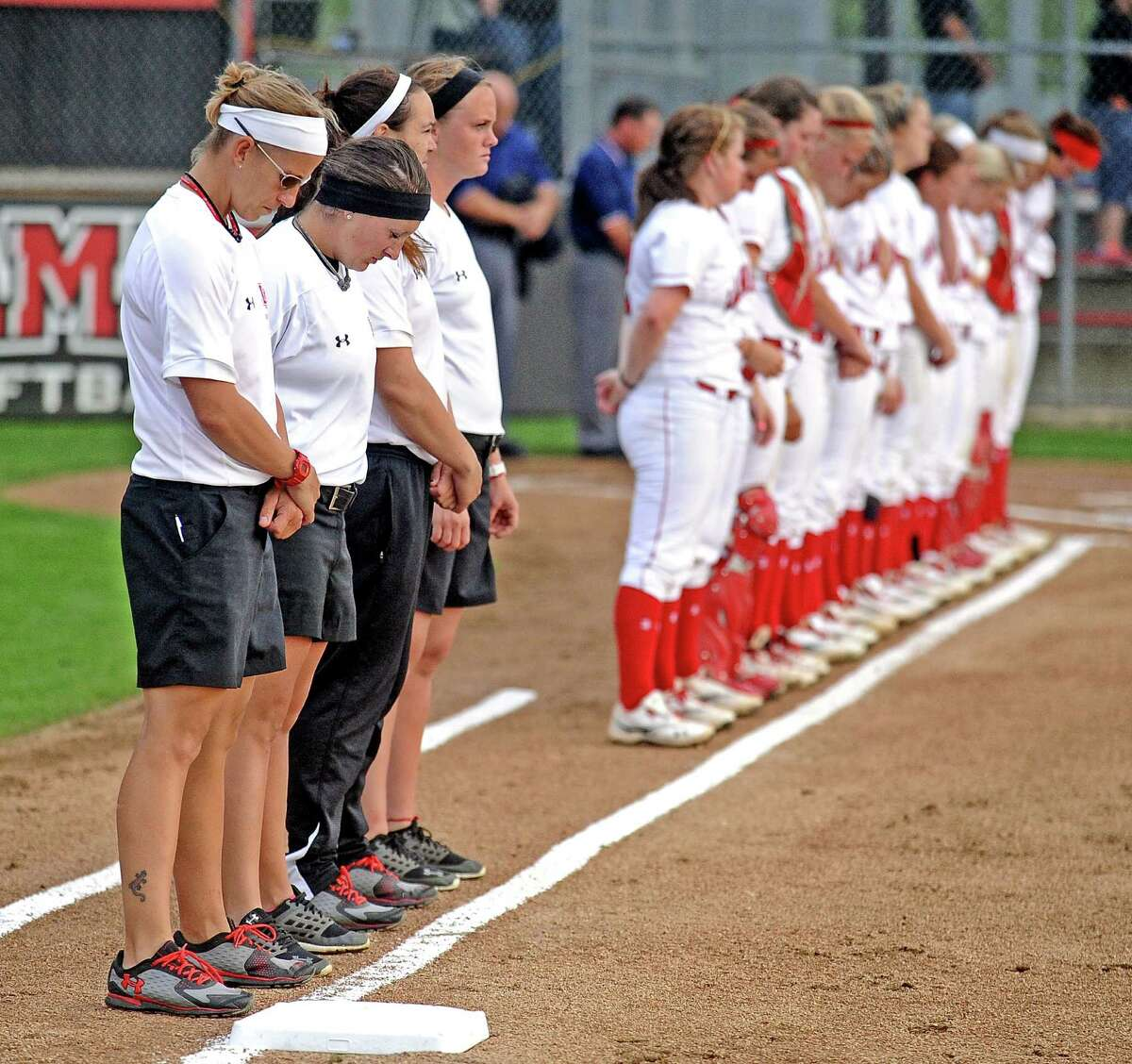 Holly Bruder, Allison Honkofsky, and Jenna Rodriguez stand with the team for a moment of silence for the Boston Marathon runners and spectators before the Lamar University Lady Cardinals softball game against Texas Souther Lady Tigers on Wednesday, April 17, 2013, at Ford Park. Photo taken: Randy Edwards/The Enterprise