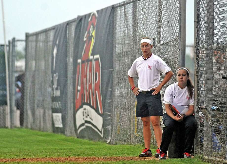 Pitching coach Jenna Rodriguez, right,and head coach Holly Bruder, left, watch the game from the dugout during the Lamar University Lady Cardinals softball game against Texas Souther Lady Tigers on Wednesday, April 17, 2013, at Ford Park.  Photo taken: Randy Edwards/The Enterprise
