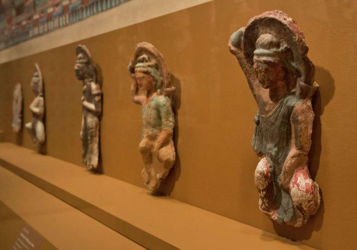 Bodhisattva holding up as lotus, right, and other sculptures of the Northern Wei Dynasty, 386-534 AD, are displayed in