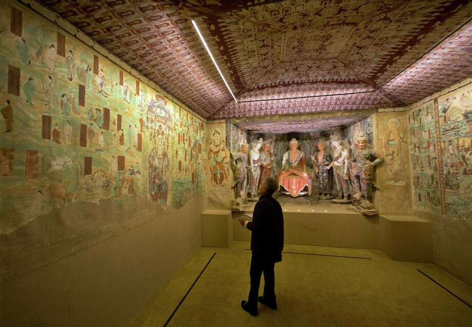 "A woman views a full scale replica cave from the 8th century that contains the Bodhisattva of the Mogao Caves, in ""Dunhuang: Buddhist Art at the Gateway of the Silk Road,"" at the China Institute, in New York,  Tuesday, April 24, 2013. Photo: Richard Drew, AP / AP"