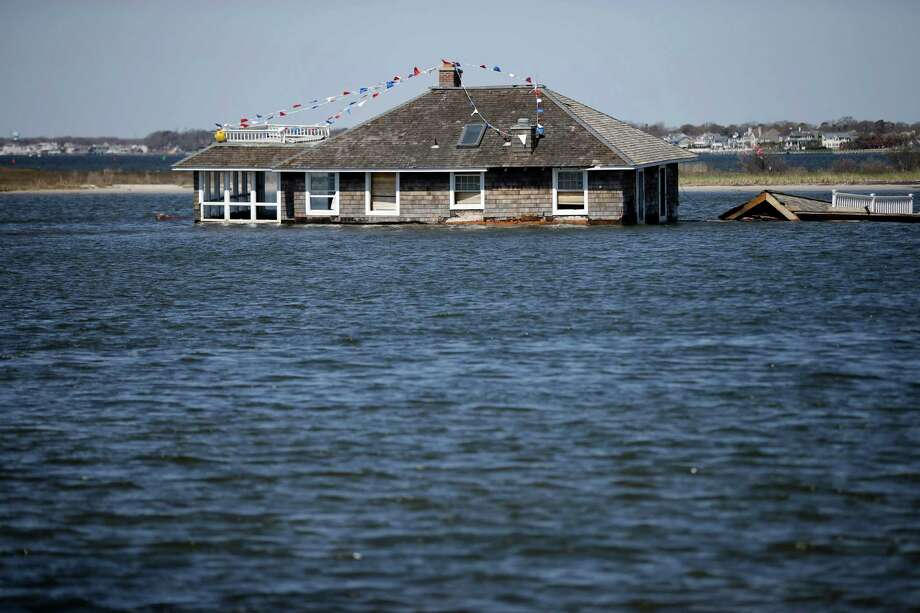 A home rests in Barnegat Bay, Thursday, April 25, 2013, in Mantoloking, N.J., after it was swept away last October by Superstorm Sandy. Six months after Sandy devastated the Jersey shore and New York City and pounded coastal areas of New England, the region is dealing with a slow and frustrating, yet often hopeful, recovery. Photo: Mel Evans, AP / AP