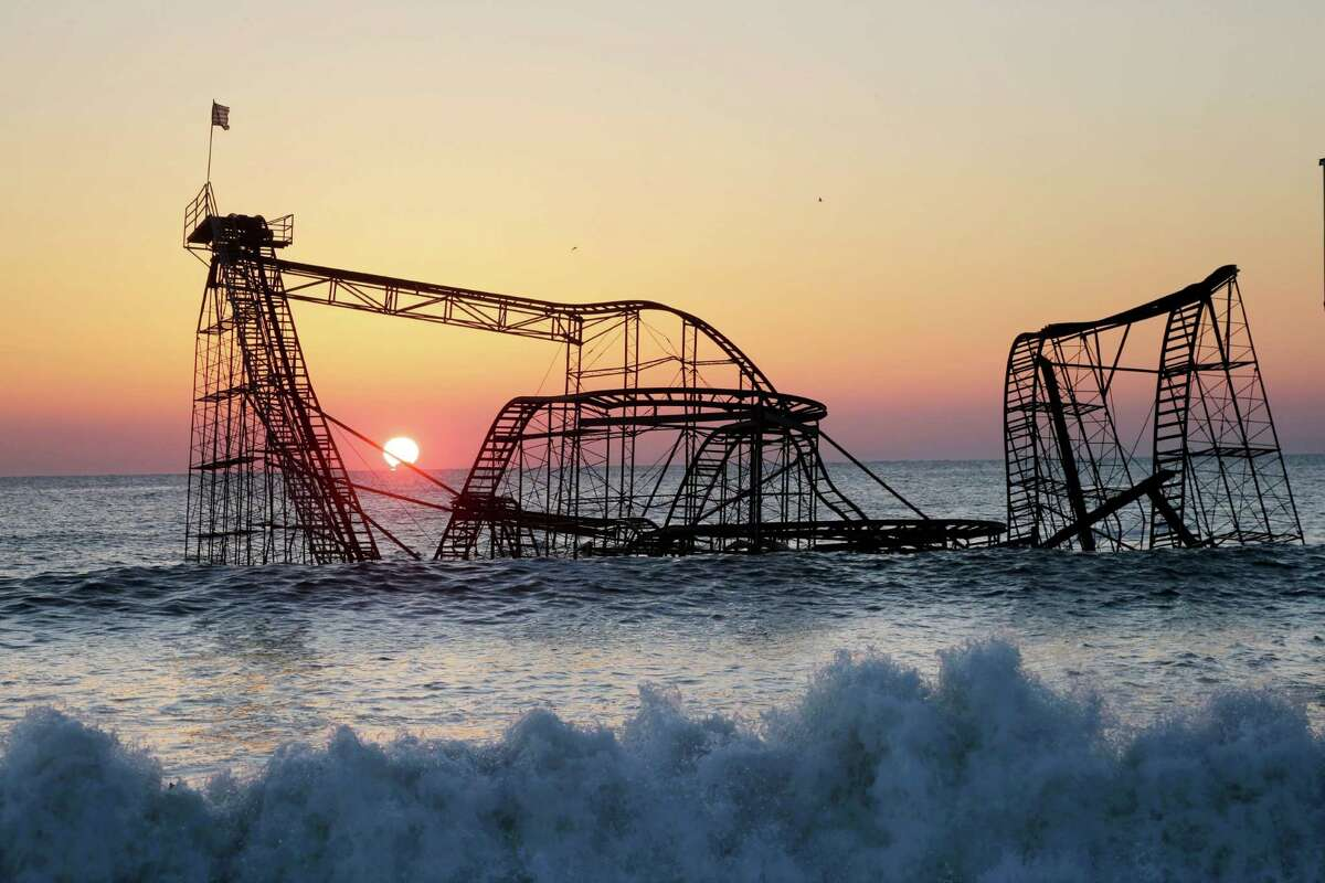 FILE - In this Feb. 25, 2013 file photo, the sun rises in Seaside Heights, N.J., behind the Jet Star Roller Coaster which has been sitting in the ocean after part of the Funtown Pier was destroyed during Superstorm Sandy. Six months after the storm, the roller coaster is still in the ocean, although demolition plans are finally moving forward.