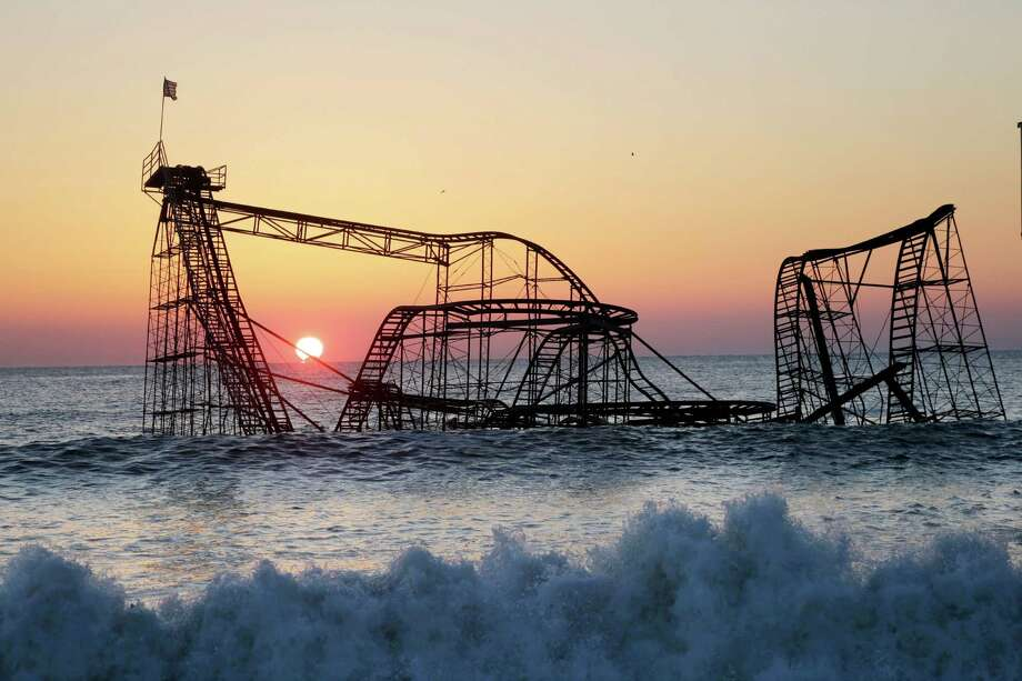 FILE - In this Feb. 25, 2013 file photo, the sun rises in Seaside Heights, N.J., behind the Jet Star Roller Coaster which has been sitting in the ocean after part of the Funtown Pier was destroyed during Superstorm Sandy. Six months after the storm, the roller coaster is still in the ocean, although demolition plans are finally moving forward. Photo: Mel Evans, AP / AP