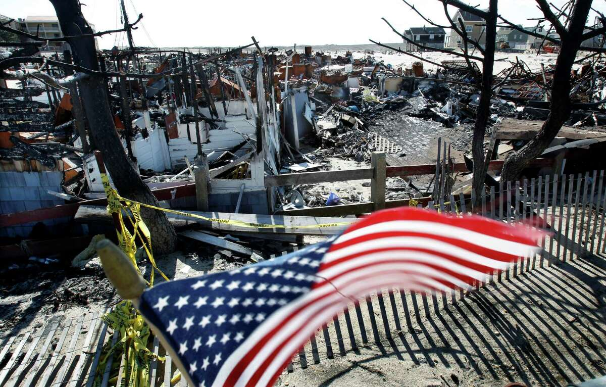 Flags decorate a fence Thursday, April 25, 2013, in Brick, N.J., around the burned remains of more than 60 small bungalows at Camp Osborn which were destroyed last October during Superstorm Sandy. Six months after Sandy devastated the Jersey shore and New York City and pounded coastal areas of New England, the region is dealing with a slow and frustrating, yet often hopeful, recovery.