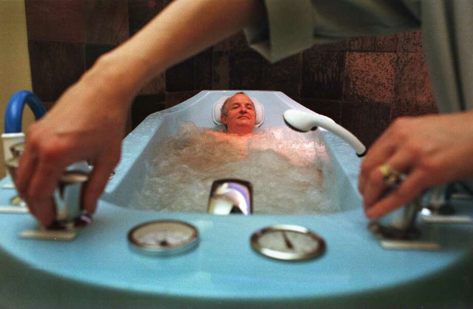 Jean Claude Simille, owner of Jean Paul Spa De Beaute', in Stuyvesant Plaza, relaxes in the hydrotherapy tub at the spa in 1998. (Paul Buckowski / Times Union) Photo: PAUL BUCKOWSKI, DG / ALBANY TIMES UNION