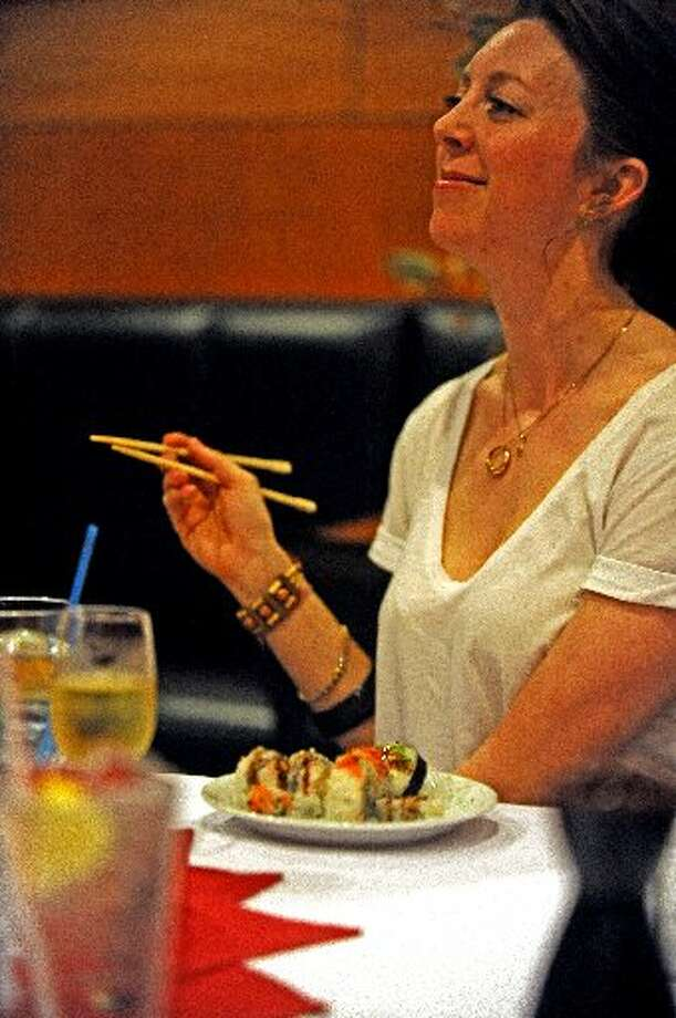 Summer Lydick listens to the description of the plate served during the Sushi 101 class at Tokyo. Randy Edwards/cat5