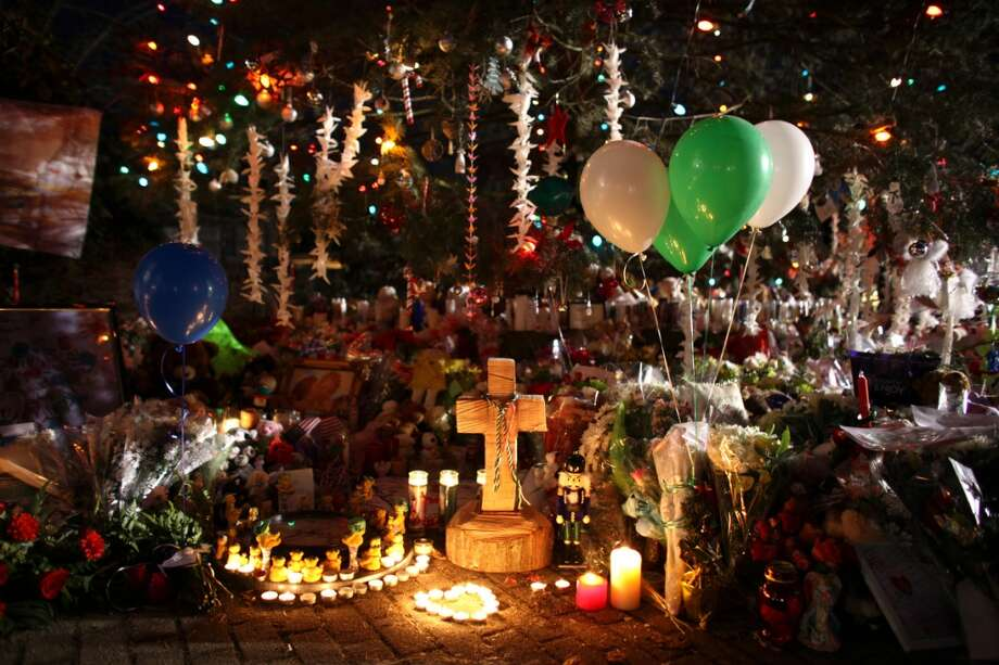Candles burn at an expanding memorial near the Sandy Hook School after a mass shooting at the school in December, 2012. The killings with a semi-automatic assault rifle rekindled the gun debate in the U.S.