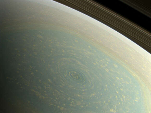 """NASA: The north pole of Saturn, in the fresh light of spring, is revealed in this color image from NASA's Cassini spacecraft. The north pole was previously hidden from the gaze of Cassini's imaging cameras because it was winter in the northern hemisphere when the spacecraft arrived at the Saturn system in 2004.   A hurricane-like storm circling Saturn's north pole at about 89 degrees north latitude is inside the famous """"hexagon"""" feature, which scientists think is a wandering jet stream that whips around the north pole at about 220 miles per hour (98 meters per second). It folds into a six-sided shape because the hexagon is a stationary wave that guides the path of the gas in the jet. The hexagon borders occur at about 77 degrees north latitude and the feature is wider than two Earths. Saturn's rings can be seen at the upper right of the image.   Images with red, green and blue spectral filters were combined to create this natural-color view, which is what the human eye would see if we were there at Saturn. The image here was acquired with the Cassini spacecraft wide-angle camera on Nov. 27, 2012 at a distance of approximately 260,000 miles (418,000 kilometers) from Saturn and at a sun-Saturn-spacecraft, or phase, angle of 96 degrees. Image scale"""