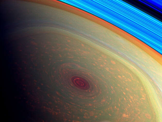 NASA: This spectacular, vertigo inducing, false-color image from NASA's Cassini mission highlights the storms at Saturn's north pole. The angry eye of a hurricane-like storm appears dark red while the fast-moving hexagonal jet stream framing it is a yellowish green. Low-lying clouds circling inside the hexagonal feature appear as muted orange color. A second, smaller vortex pops out in teal at the lower right of the image. The rings of Saturn appear in vivid blue at the top right.   The images were taken with Cassini's wide-angle camera using a combination of spectral filters sensitive to wavelengths of near-infrared light. The images filtered at 890 nanometers are projected as blue. The images filtered at 728 nanometers are projected as green, and images filtered at 752 nanometers are projected as red. At Saturn, this scheme means colors correlate to different altitudes in the planet's polar atmosphere: red indicates deep, while green shows clouds that are higher in altitude. High clouds are typically associated with locations of intense upwelling in a storm. These images help scientists learn the distribution and frequencies of such storms. The rings are bright blue in this color scheme because there is no methane gas between the ring particles and the camera.   The view was acquired at a distance of approximately 261,000 miles (419,000 kilometers) from Saturn and at a sun-Saturn-spacecraft, or phase, angle of 94 degrees. Image scale is 13 miles (22 kilometers) per pixel. Photo: NASA