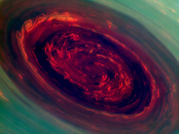 NASA: The spinning vortex of Saturn's north polar storm resembles a deep red rose of giant proportions surrounded by green foliage in this false-color image from NASA's Cassini spacecraft. Measurements have sized the eye at a staggering 1,250 miles (2,000 kilometers) across with cloud speeds as fast as 330 miles per hour (150 meters per second).   This image is among the first sunlit views of Saturn's north pole captured by Cassini's imaging cameras. When the spacecraft arrived in the Saturnian system in 2004, it was northern winter and the north pole was in darkness. Saturn's north pole was last imaged under sunlight by NASA's Voyager 2 in 1981; however, the observation geometry did not allow for detailed views of the poles. Consequently, it is not known how long this newly discovered north-polar hurricane has been active.   The images were taken with the Cassini spacecraft narrow-angle camera on Nov. 27, 2012, using a combination of spectral filters sensitive to wavelengths of near-infrared light. The images filtered at 890 nanometers are projected as blue. The images filtered at 728 nanometers are projected as green, and images filtered at 752 nanometers are projected as red. In this scheme, red indicates low clouds and green indicates high ones.   The view was acquired at a distance of approximately 261,000 miles (419,000 kilometers) from Saturn and at a sun-Saturn-spacecraft, or phase, angle of 94 degrees. Image scale is 1 mile (2 kilometers) per pixel. The Cassini-Huygens mission is a cooperative project of NASA, the European Space Agency and the Italian Space Agency. NASA's Jet Propulsion Laboratory, a division of the California Institute of Technology in Pasadena, manages the mission for NASA's Science Mission Directorate, Washington, D.C. The Cassini orbiter and its two onboard cameras were designed, developed and assembled at JPL. The imaging operations center is based at the Space Science Institute in Boulder, Colo. Photo: NASA