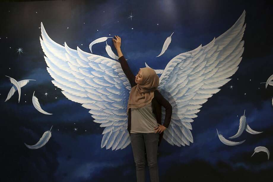 If it's good enough for Victoria's Secret models ...A Muslim woman tries on a pair of mural wings for size at an 