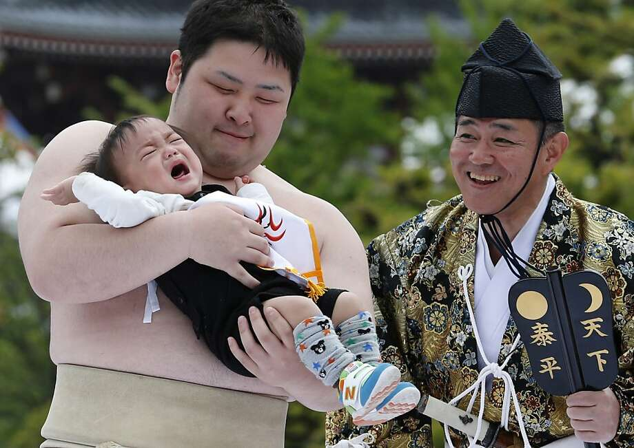Somebody needs a diaper change - hopefully it's the kid: In Naki Sumo (Crying Baby Contest) - a traditional rite performed as a 
