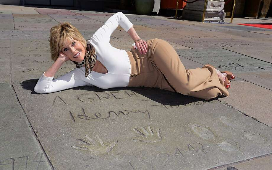 Like father, like daughter:Jane Fonda lies besides father Henry Fonda's hand and shoe prints at the TCL 