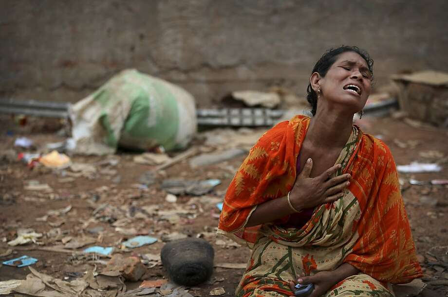 A woman cries out for her missing husband at the site of the garment factory building that collapsed 